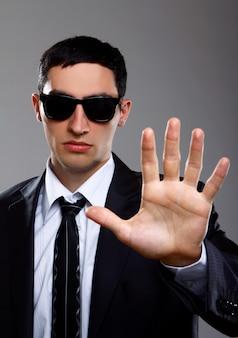 スーツの深刻な男は一時停止の標識を示しています