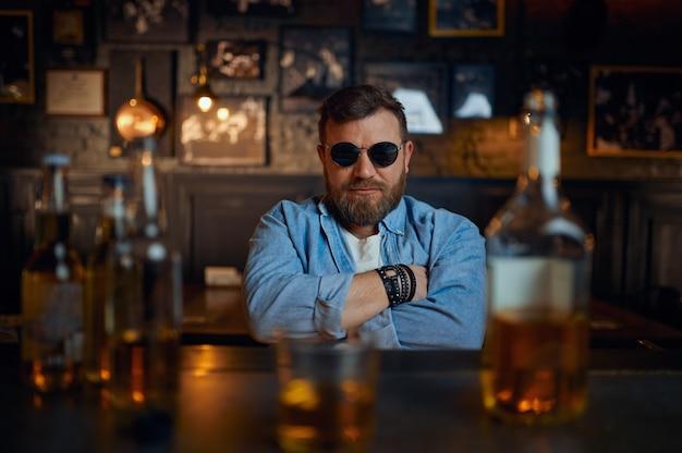 Серьезный мужчина в солнцезащитных очках сидит за стойкой в баре. один мужчина отдыхает в пабе, человеческие эмоции, досуг, ночная жизнь