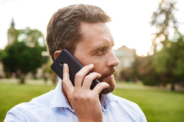 흰색 셔츠에 심각한 남자, 검은 스마트 폰에서 이야기하는 동안 녹색 공원에서 산책하는 동안 옆으로 찾고
