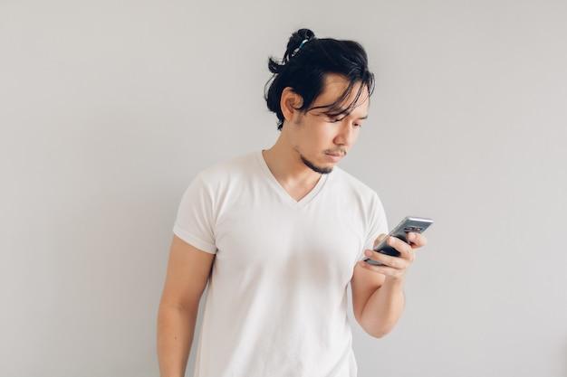 白いtシャツを着た真面目な男が灰色の壁にスマートフォンを使用しています