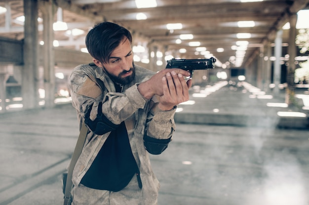 Serious man is standing in hangar and holding paintball gun in hands.