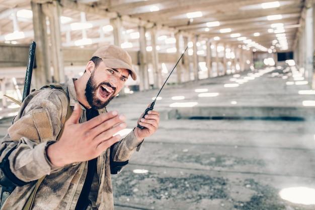 深刻な男は格納庫に立って、ペイントボール銃を手に持っています。