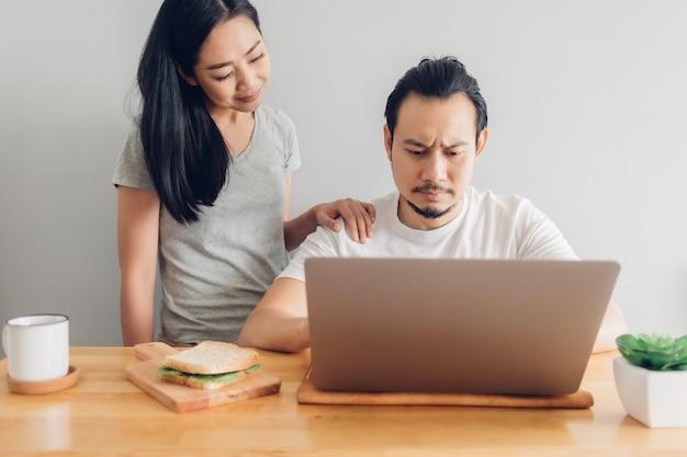 심각한 남자는 집에서 일의 개념에 그의 아내 지원과 함께 일하고 있습니다.