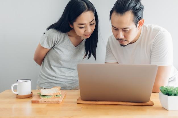 深刻な男性は、自宅での仕事の概念で彼の妻のサポートと一緒に働いています。