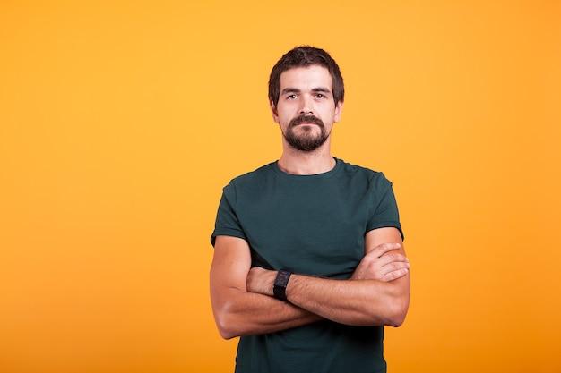 オレンジ色の背景に分離された深刻な男。カメラを見て自信のある人