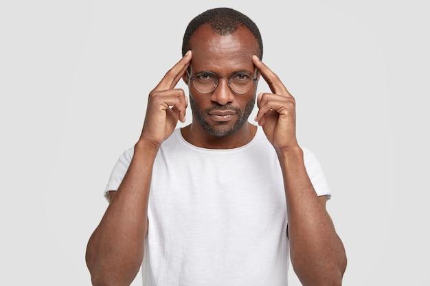L'uomo serio tiene le mani sulle tempie, cerca di concentrarsi su qualcosa, vestito con una maglietta bianca casual, sta al coperto, ricorda le informazioni