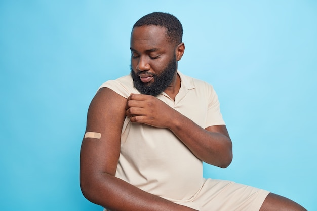 Serious man looks at arm with plaster got vaccinated during coronavirus panemic sits indoor against bluewall
