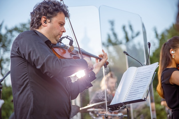 Serious man musician looking at musical notebook with notes and playing violin outdoors