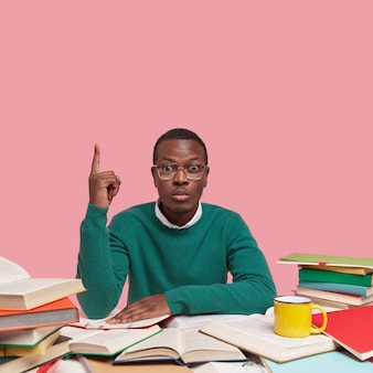 Serious man nerd wears big spectacles, green sweater, points up with one finger, surrounded with many books as prepares for examination session