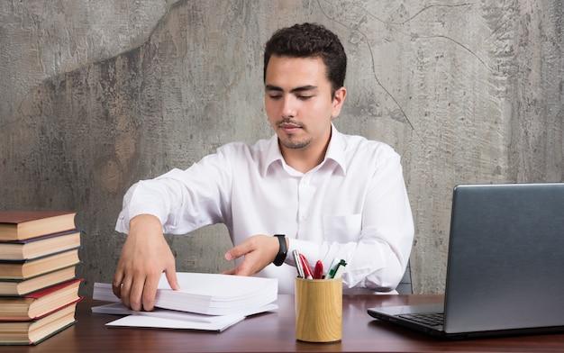 Серьезный мужчина систематизирует документы за офисным столом.