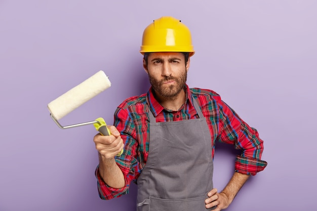 Serious man painter holds painting roller, does redecoration at home, paints walls, wears protective helmet and apron, poses indoor, busy with repairing and renovation, isolated on purple wall.