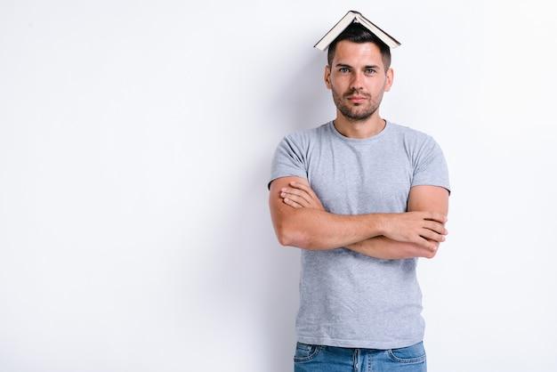 머리에 책을 얹고 팔짱을 끼고 서 있는 동안 카메라를 바라보는 진지한 남자. 흰 벽에 고립된 쾌활한 남자의 이미지