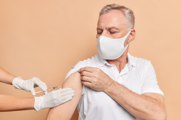 Serious man received second dose of coronavirus vaccine wants to bring pandemic to end looks attentively at process of injection wears protective face mask casual t shirt