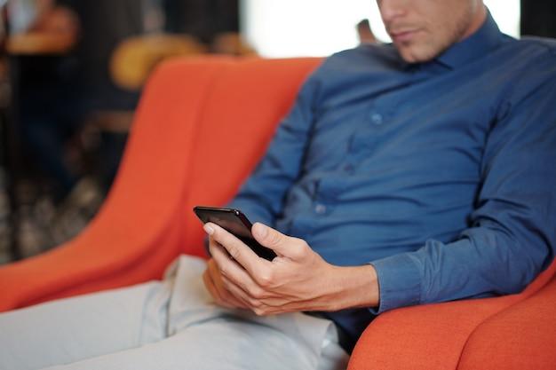 カフェの肘掛け椅子でリラックスし、彼のスマートフォンでニュースやテキストメッセージを読んで真面目な男