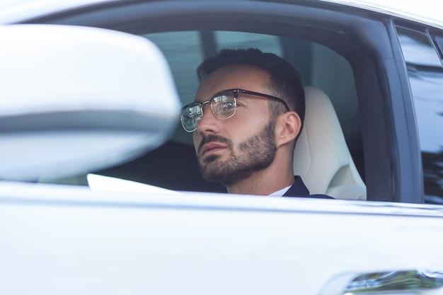 真面目な男。オフィスに向かって車を運転している眼鏡をかけている深刻なひげを生やした男