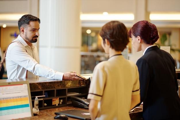 호텔 리셉션에서 매니저에게 스마트폰으로 예약 정보를 보여주는 진지한 남자