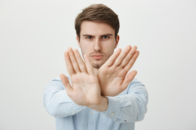 Serious man showing stop gesture, restrict or forbid action
