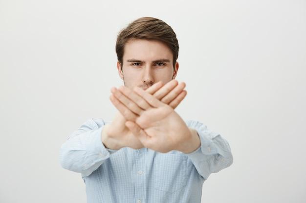 停止ジェスチャーを示す深刻な男、アクションを制限または禁止