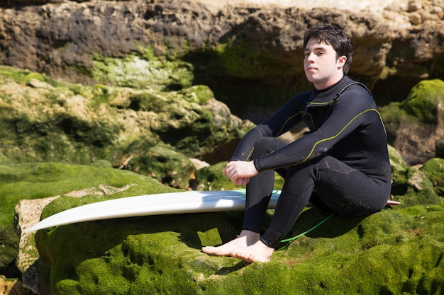 Serious man sitting on mossy rocks with surfboard