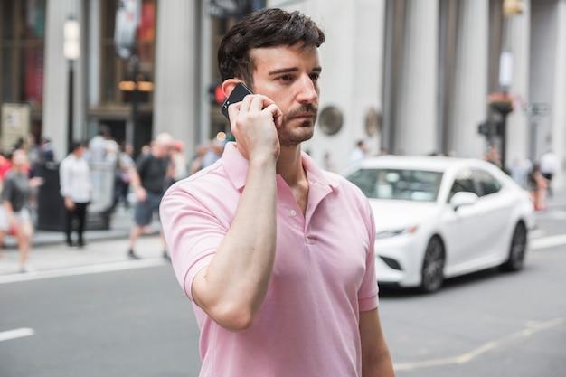 Serious man speaking on smartphone