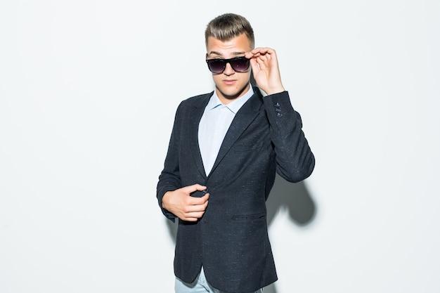 Uomo serio in suite in posa in occhiali da sole moderni davanti alla parete chiara