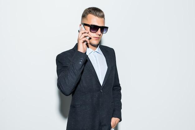 Uomo serio in suite e colloqui di occhiali da sole sul suo telefono davanti alla parete chiara