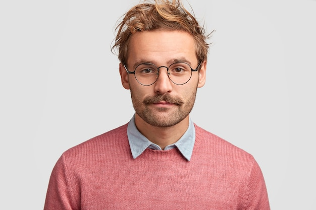 Serious man teacher with confident clever look, has beard and mustache, listens pupil`s answer, wears pink sweater, round glasses