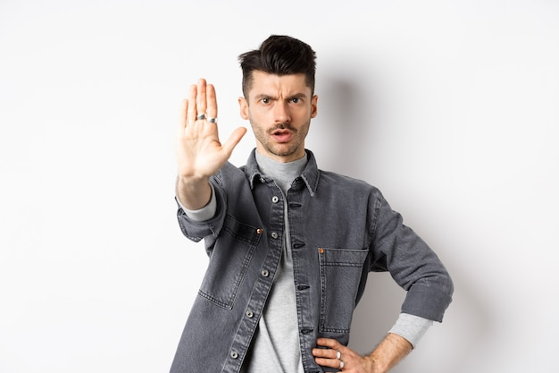 Serious man tell to stop, prohibit something and frowning, say no, standing displeased with stretch out hand against white background.