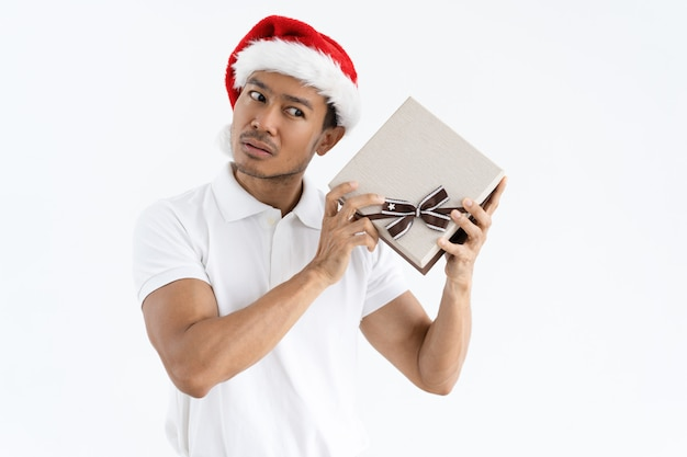 Serious man trying to guess what is inside christmas gift box