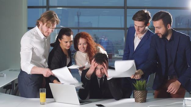 職場でのストレスの下で深刻な男。同僚が彼の顔で紙を振る