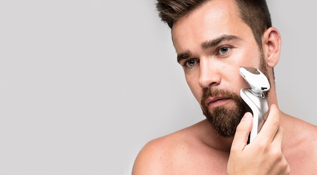 Serious man using an electric shaver with copy space