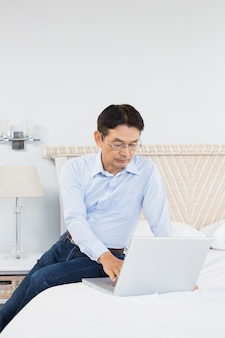 Serious man using laptop in bedroom