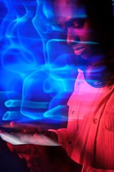 Серьезный человек, использующий смартфон в неоновом размытом дыме