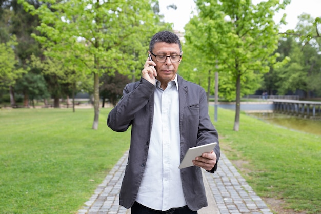 Serious man using tablet and talking on phone in park