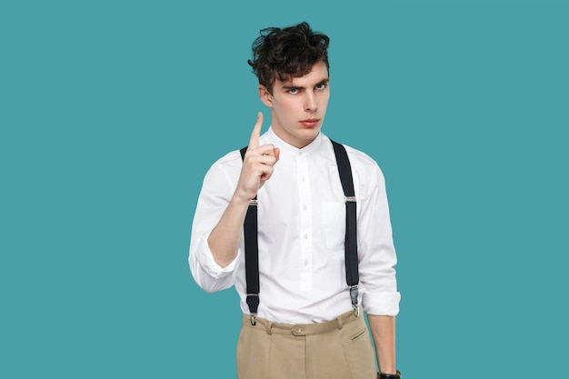 Serious man warning sign looking at camera. portrait of handsome hipster curly young businessman in classic casual white shirt and suspender standing. indoor studio shot isolated on blue background.