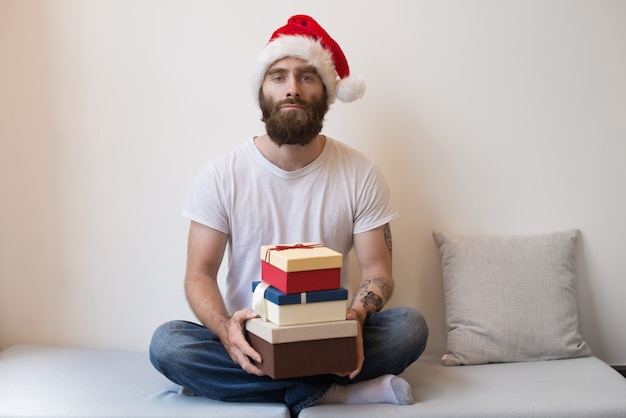 Serious man wearing santa hat and holding gift boxes on couch