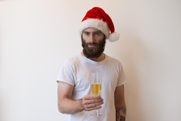 Serious man wearing santa hat and holding goblet with champagne