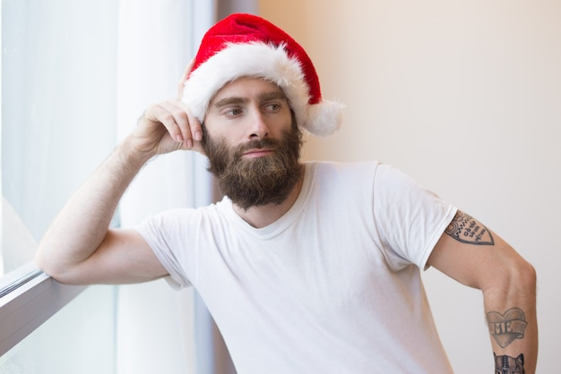 Serious man wearing santa hat and leaning on window frame