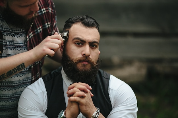 Serious man while shaving him