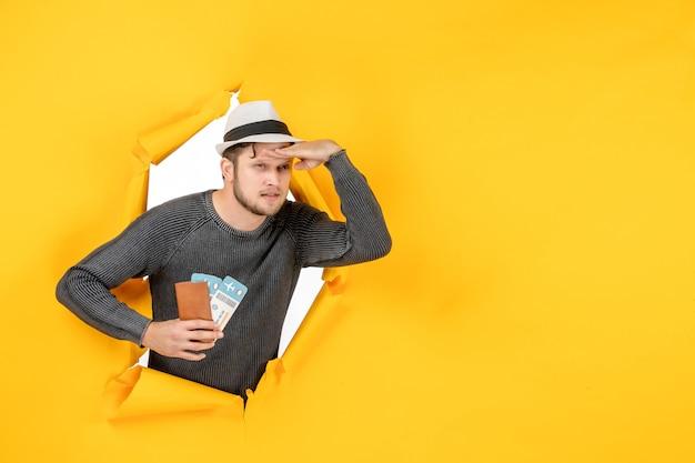 티켓과 함께 외국 여권을 들고 노란색 벽에 찢어진 무언가에 집중된 모자를 가진 심각한 남자