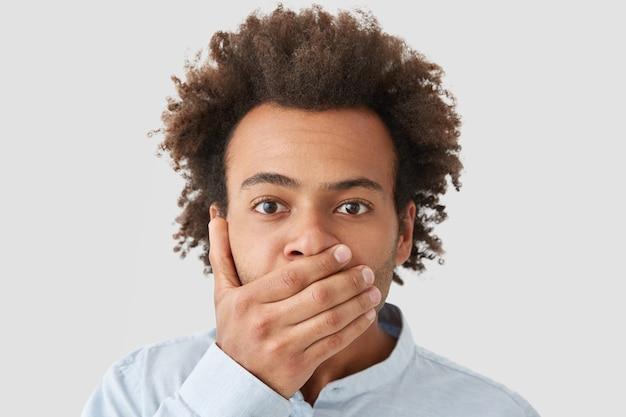 Uomo serio con taglio di capelli afro, copre la bocca con il palmo, essendo senza parole, mantiene le informazioni nell'intrigo
