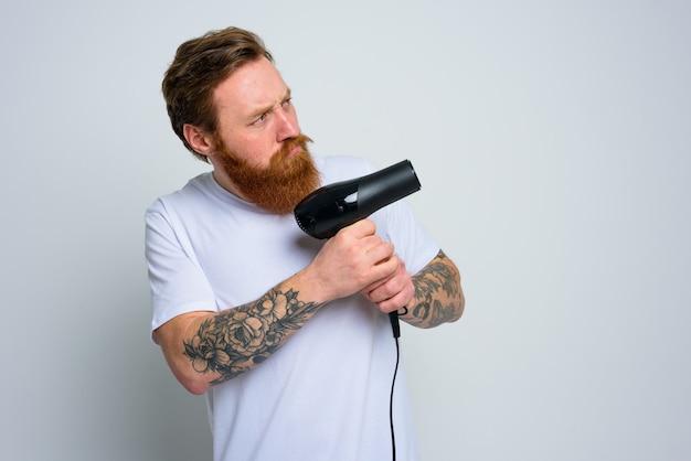 Серьезный мужчина с бородой играет с феном для волос