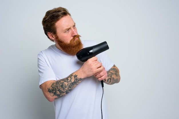Serious man with beard play with hair dryeras a handgun