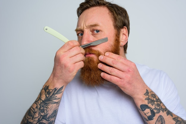 Serious man with blade is focused on cutting his beard