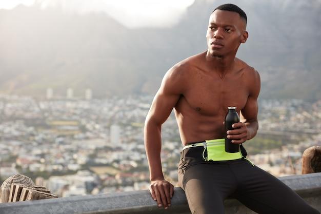 어두운 피부를 가진 진지한 남자는 산에서 익스트림 스포츠를하고 신선한 음료를 병에 들고 생각에 깊이 빠져 미래의 목표에 대해 생각하며 건강한 활동적인 라이프 스타일을 이끌고 있습니다. 피트니스 남성 모델.