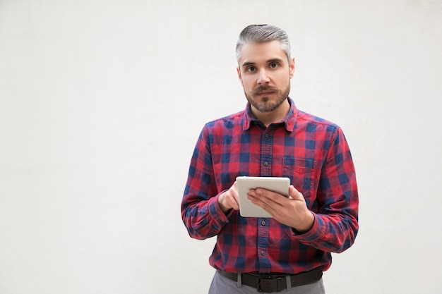 Serious man with digital tablet looking