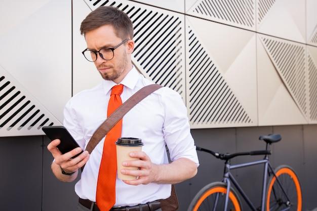 建物の外に向かって屋外に立っている間、休憩中に連絡先を見てコーヒーとスマートフォンのガラスを持つ深刻な男
