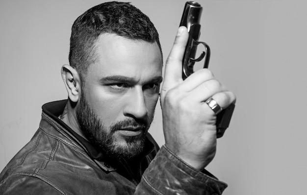 Серьезный человек с пистолетом готов стрелять. сосредоточен на цели. копировать пространство.
