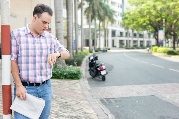 Serious man with newspaper checking time on street