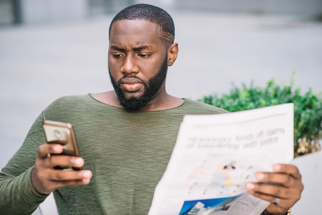 Serious man with newspaper using smartphone